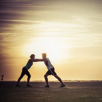 Caucasian couple stretching in desert
