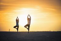 Caucasian couple practicing yoga in desert