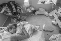 Caucasian teenage girl laying on bed