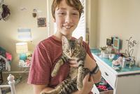 Caucasian boy holding cat in bedroom