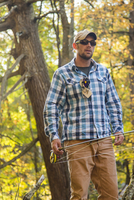 Caucasian man carrying fishing rod under tree