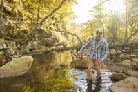 Caucasian man walking in forest stream