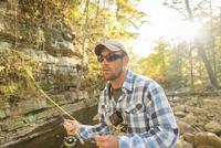 Caucasian man fishing in forest stream