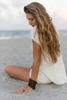Hispanic woman sitting on beach