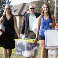 Caucasian parents helping daughter move into college dormitory