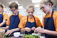 Students tearing herbs in cooking class