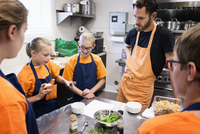 Teacher and students working in cooking class
