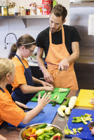 Teacher and students chopping vegetables in cooking class