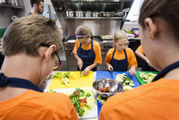 Students chopping vegetables in cooking class