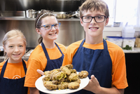 Students holding food in cooking class