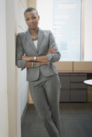 Black woman standing with arms crossed in office