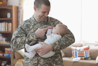 Caucasian soldier holding baby daughter