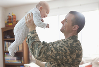 Caucasian soldier lifting baby daughter
