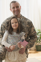 Caucasian soldier hugging daughter