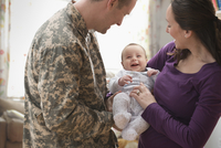 Caucasian soldier and wife holding baby daughter
