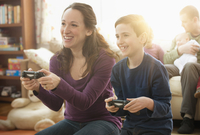 Caucasian mother and son playing video games