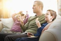 Caucasian father and children eating snacks on sofa 11018059846| 写真素材・ストックフォト・画像・イラスト素材|アマナイメージズ