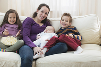 Caucasian mother and children relaxing on sofa