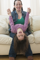 Caucasian mother and daughter playing on sofa