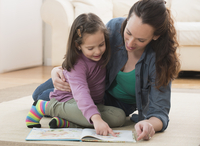 Caucasian mother and daughter reading on floor