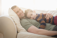 Caucasian father and son hugging on sofa