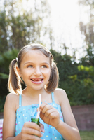 Smiling girl eating candy cigarette in backyard
