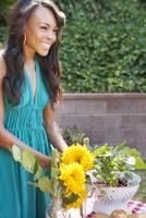 Smiling woman gathering flowers in backyard
