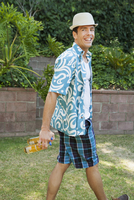 Man carrying cans of beer in backyard