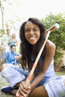 Smiling woman holding croquet mallet in backyard