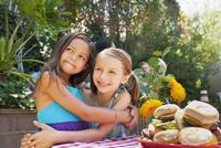 Girls hugging at backyard barbecue
