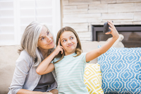 Caucasian grandmother and granddaughter taking selfie with cell phone