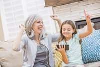 Caucasian grandmother and granddaughter listening to cell phone