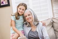 Caucasian grandmother and granddaughter hugging on sofa