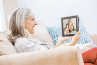 Caucasian grandmother videochatting with granddaughter on digital tablet