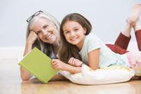 Caucasian grandmother and granddaughter reading book