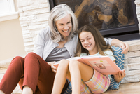 Caucasian grandmother and granddaughter reading book by fireplace