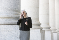 Caucasian businesswoman talking on cell phone under columns