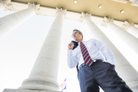 Low angle view of mixed race businessman standing under columns