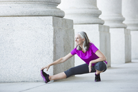 Caucasian woman stretching outside courthouse