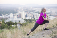 Caucasian woman stretching on hilltop over Salt Lake City, Utah, United States