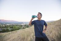Mixed race man drinking water bottle on hilltop