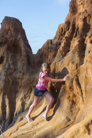 Caucasian girl climbing rock formations