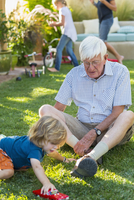 Caucasian grandfather and grandson playing on lawn