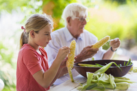 Caucasian grandfather and granddaughter shucking corn