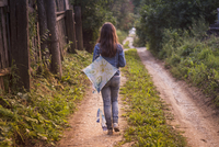 Caucasian teenage girl carrying kite on dirt road