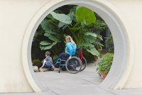Paraplegic mother and son admiring plants