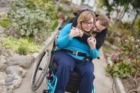 Man hugging paraplegic girlfriend in garden