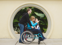 Man pushing paraplegic wife and son