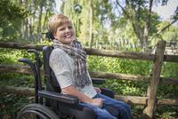 Paraplegic woman in wheelchair smiling in garden