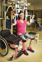 Paraplegic woman working out in physical therapy
